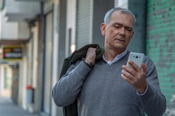 attractive adult man using mobile phone on the street