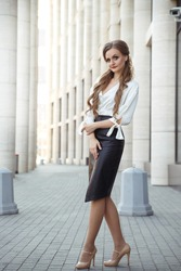 Attractive adult woman in elegant business attire in full length outside.
