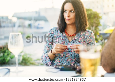 attractive adult women rolling a cigarette on a coffee shop table outdoor. Mid-aged adults lifestyle concept