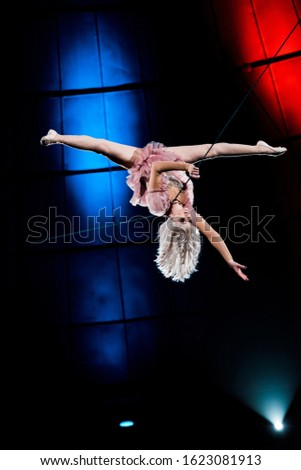 attractive aerial acrobat doing splits while performing in circus