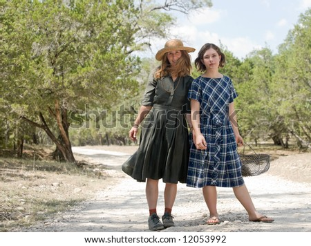 Attractive, affectionate mother and daughter holding hands, enjoying a stroll on a rural dirt road.
