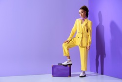 attractive african american girl posing in yellow suit with purple suitcase, on trendy ultra violet background