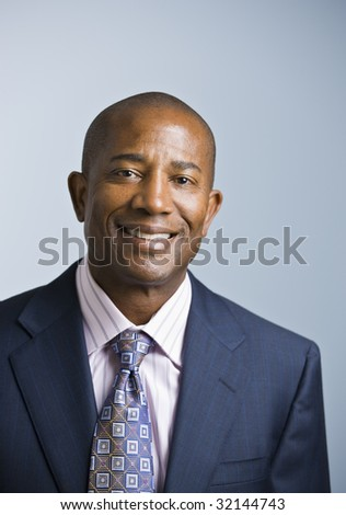 Attractive African American headshot dressed in a suit and tie, facing the camera. vertical