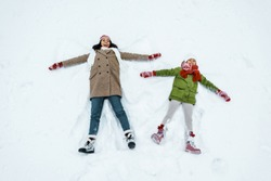 attractive african american mother and cute daughter doing snow angels in winter forest