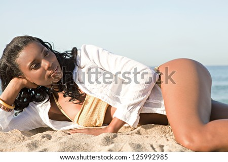 Attractive african american woman laying down on a golden sand beach by the sea shore, relaxing and sunbathing during a summer day.