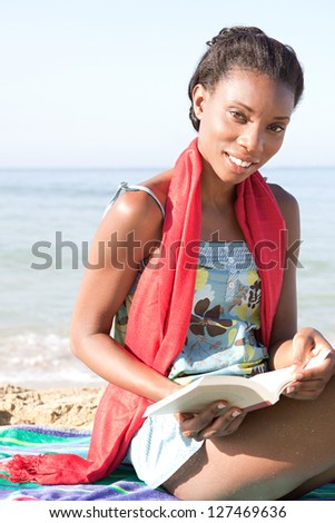 Attractive african-american woman reading a book while sitting on a stripy towel on a golden sand beach while on vacation, smiling.
