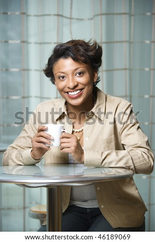Attractive African-American woman sits at a table. She is holding a coffee cup and smiling towards the camera. Vertical shot.