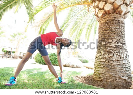 Attractive african american woman stretching after doing sport in the city under a palm tree, training for fitness.