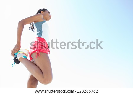 "Attractive ""african american"" woman stretching her legs while standing against a deep blue sky, exercising on a sunny day."