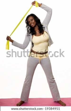Attractive African American woman wearing workout attire standing on pink exercise mat stretching