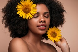 Attractive African American woman with closed eyes and sunflowers in hair enjoying vitamin E benefits against brown background