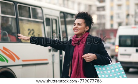 Attractive african american woman with shopping bags talking phone while waiting for taxi cab and coming back from mall sales