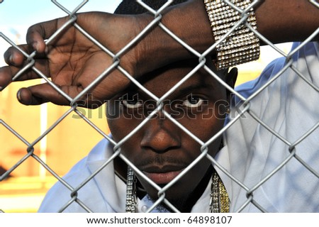 Attractive African American young man revealing his anger and depression while leaning against a chain link fence.