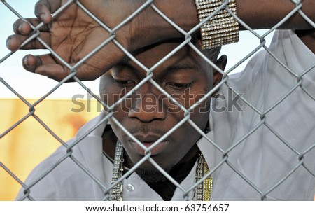 Attractive African American young man revealing his sadness and depression while leaning against a chain link fence.
