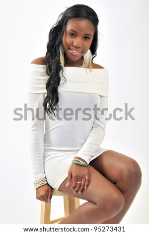Attractive African-American young woman in white dress - model in studio - smiling and sitting on a stool