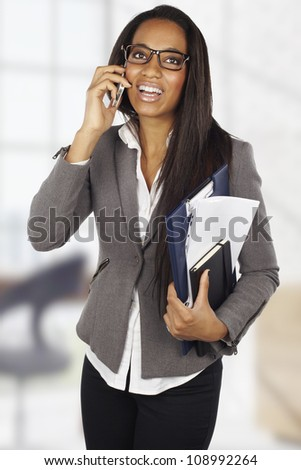 attractive african businesswoman with mobile phone at office