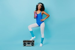 Attractive african lady in aerobics outfit standing on boombox. Studio shot of wonderful black girl drinking water after training.
