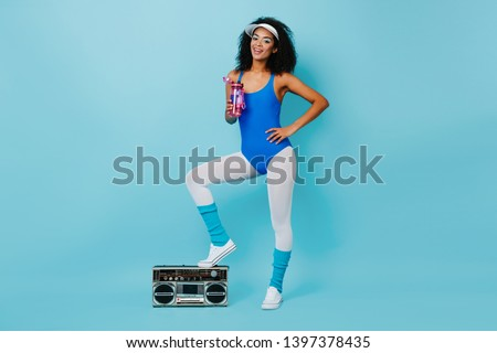 Attractive african lady in aerobics outfit standing on boombox. Studio shot of wonderful black girl drinking water after training. Photo stock ©