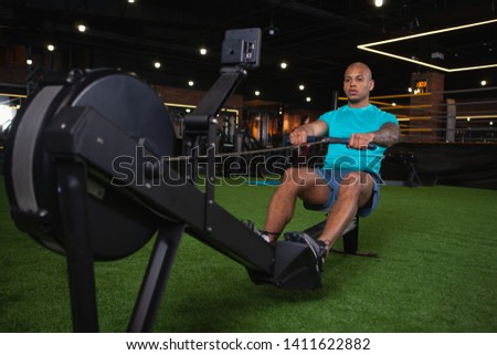 Attractive African male athlete exercising on rowing machine at the gym. Handsome young sportsman concentrating, rowing at sport studio. Energy, endurance concept