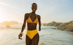 Attractive african woman in yellow bikini walking along the beach. Smiling female in swimwear coming out of the sea water at sunset.