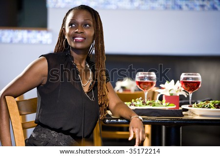 Attractive African woman sitting at a table in restaurant