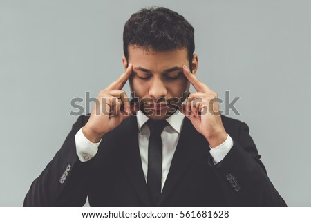 Attractive Afro American businessman in classic suit is touching his temples while concentrating, on gray background