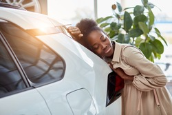 attractive afro woman dreams about new car, young female came to see automobiles, make purchase. woman is leaned on white luxurious car, smiling