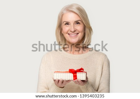 Attractive aged blond woman looks at camera holding presents gift box red bow package feels happy studio head shot isolated on grey background. Life events celebration congratulation love care concept
