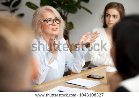 Attractive aged businesswoman, teacher or mentor coach speaking to young people, senior woman in glasses teaching audience at training seminar, female business leader speaker talking at meeting