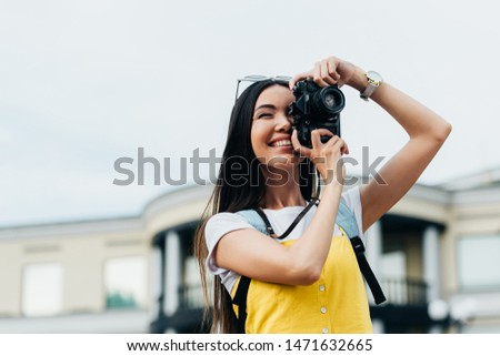 attractive and asian woman with glasses smiling and taking photo
