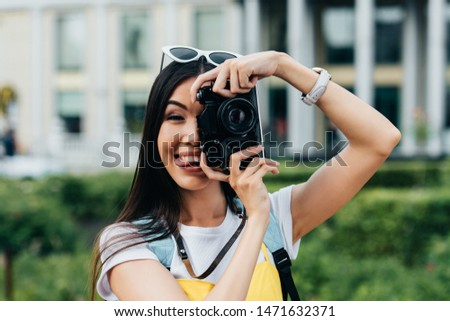 attractive and asian woman with glasses sticking out tongue and taking photo