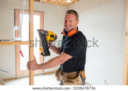 attractive and confident constructor carpenter or builder man working wood with electric drill at industrial construction site in installation and renovation work industry #1038678736