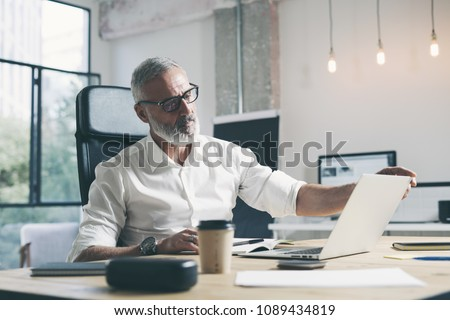 Attractive and confidental adult businessman using mobile laptop computer while working at the wooden table at modern coworking office