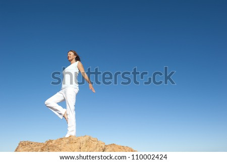 Attractive and fit mature woman standing confident and concentrated on top of a rock, balancing and exercising on one leg, isolated with blue sky as background and copy space.