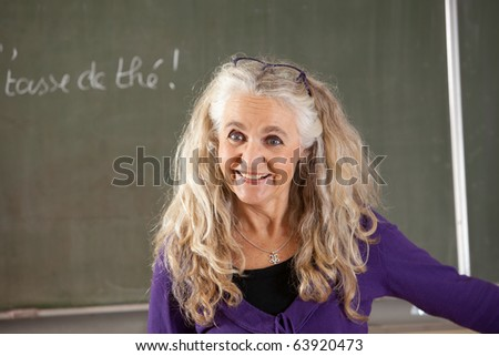 Attractive and friendly teacher in front of chalkboard in class