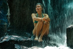 attractive and happy mid adult woman with grey hair 40s or 50s enjoying blissful and free at beautiful tropical waterfall feeling the purity and beauty of nature wet under the falling water