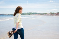 Attractive and happy middle aged woman walking along the seashore holding the shoes in hand