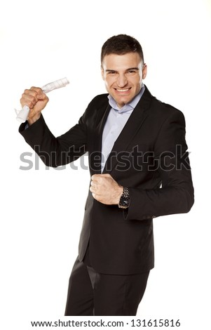 attractive and happy young businessman with triumphs with paper in hand