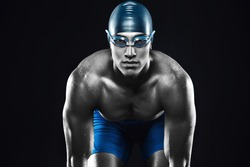 Attractive and muscular swimmer ready to jump into water. Studio shot of young shirtless sportsman on black background. Man with glasses. Monochrome image