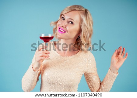attractive and smiling blonde woman chic make-up and hairstyle in a in evening cocktail dress holding glass of red wine in the studio on a blue background. concept of party 2019 new year