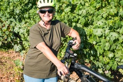 Attractive and smiling senior woman with white hair takes a break in the middle of the bunches of grapes. E bike close to her, for healthy lifestyle. One happy people.Green vineyard in background.