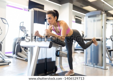 Attractive and sporty woman looking away while doing leg exercise in health club