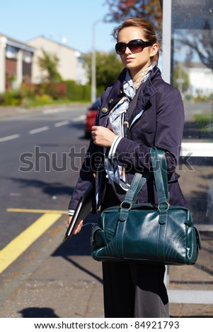 Attractive and trendy businesswoman wait for bus, street shoot