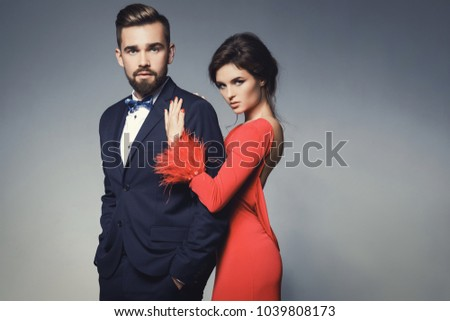Attractive and well-dressed couple posing in studio. Woman in beautiful red dress and man wearing blue classical suit with bow tie. #1039808173