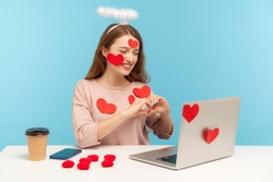 Attractive angelic woman with kind expression sitting covered with sticker love hearts, showing romantic heart shape with hands to laptop screen, dating on video call. indoor studio shot, isolated