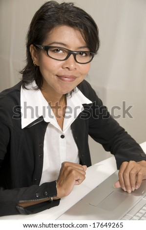 Attractive Asian business woman looking at camera and smiling
