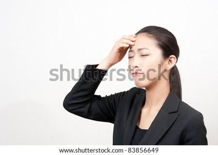 attractive asian businesswoman having headache