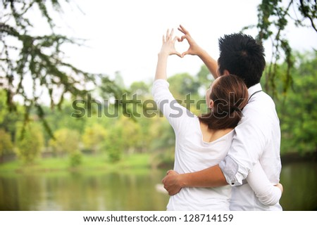 Attractive Asian Couple making a love symbol with hands