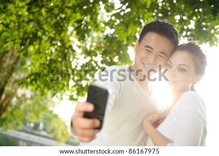 Attractive asian couple one smiling Taking Photographs in the park