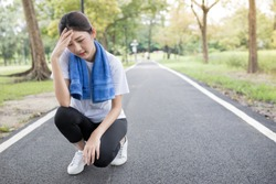 attractive asian female headache and dizziness after running  in public park, health promotion